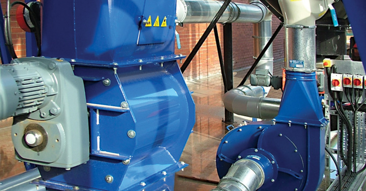 A rotary valve allows waste to be discharged into a closed-loop conveying system