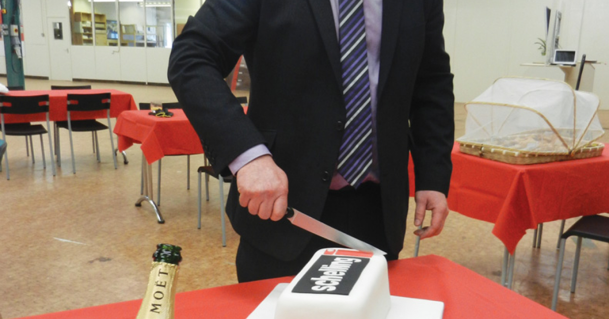 Schelling UKMD Markus Freuis cutting the celebratory cake after a fine lunch with visitors and friends