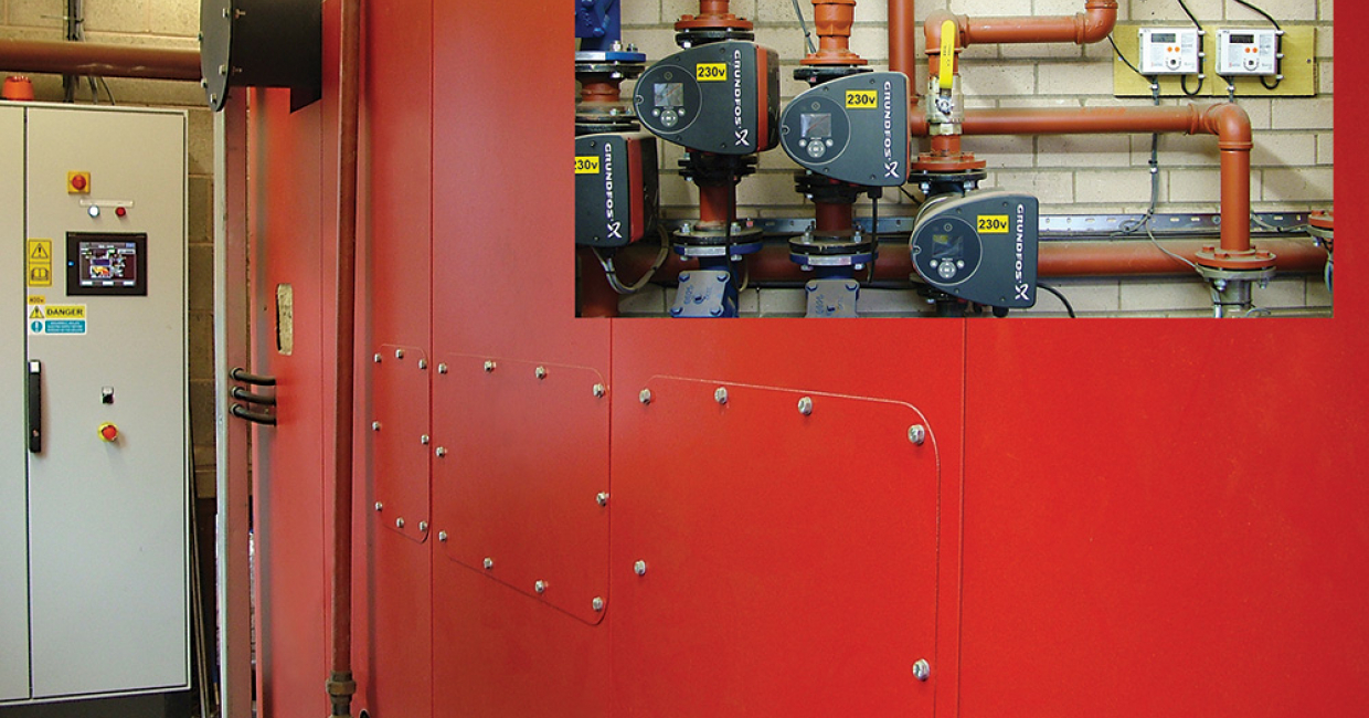 A compact boiler room houses the DCS 300kW biomass boiler, along with control panel, pumps and meters recording kilowatt hours of generated heat